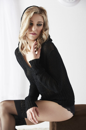foreplay: Sexy and beautiful young adult caucasian woman in black lingerie and a knitted see through hoodie in a light white bedroom