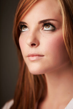 auburn: Beautiful young caucasian adult woman with long auburn red hair on a plain background, wearing a white button shirt.