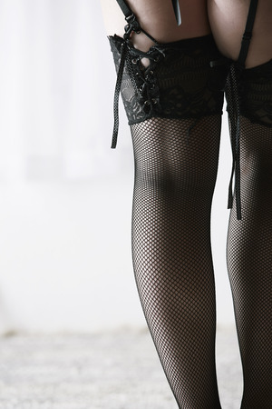 Beautiful, voluptuous and sexy caucasian adult woman in black fishnet stockings and garters in a boudoir setting lit from the side with window light. photo