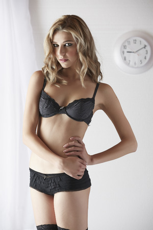 Sexy and beautiful young adult caucasian blonde woman in black lingerie in a light white bedroom photo