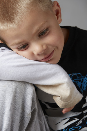 light complexion: 5 year old caucasian boy with short blonde hair, blue eyes and a light, healthy complexion wearing a long sleeve t-shirt  Shot in studio on a grey background