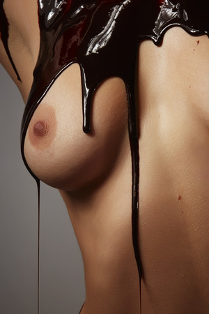 Thick dark chocolate sauce running down the breast of an adult caucasian woman�s breast and torso photo