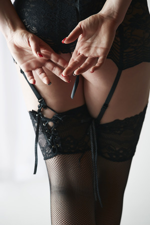 erotico: Bella, indoeuropea adulta donna voluttuosa e sexy in calze a rete nere e giarrettiere in un ambiente boudoir illuminato dal lato con la luce della finestra.