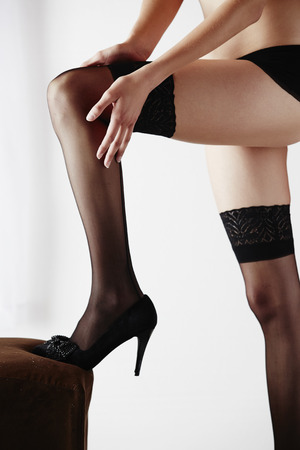 to undress: The legs of a sexy and beautiful young adult caucasian woman in black lingerie and stockings in a light white bedroom