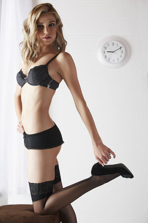 foreplay: Sexy and beautiful young adult caucasian blonde woman in black lingerie and stockings in a light white bedroom
