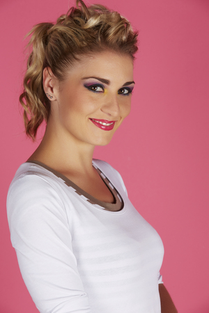 Portrait of a beautiful young adult caucasian woman with blonde hair and casual white shirt with glamorous makeup and a formal hairstyle on a pink background photo