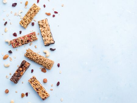 Granola bar on blue background. Set of different granola bars on white marble table. Shallow DOF. Top view or flat lay. Copy space for text.