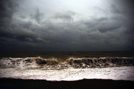 wzburzone morze: Widok na morze szorstki i ciemne niebo od plaży