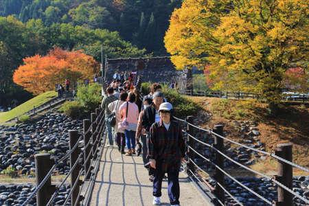 ogimachi: people cross the bridge over Shogawa river to the Ogimachi Village