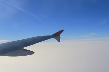 Wing of the plane on sky background - plane wing with cloud patterns  photo