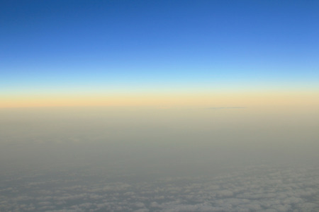 Spectacular view of a sunset above the clouds from airplane window photo