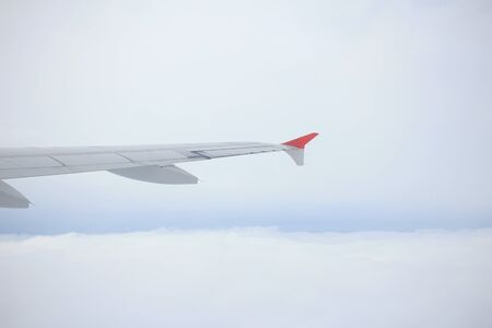 though: a view though an airplane window where one can see the wing and beautiful cloudy sky Stock Photo