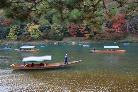 Unidentified people sail boates in the Oi river for tourist