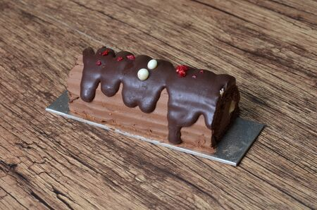 billet: the Raspberry Chocolate Log Cake at wood background Stock Photo