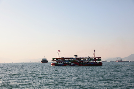 victoria harbor: ferry on Victoria harbor in Hong Kong with tall buildings. Stock Photo