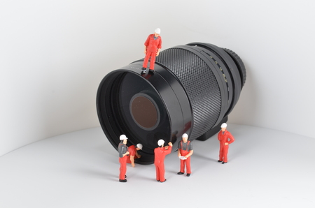 photojournalism: the  image of mini figure dolls work with lens Stock Photo