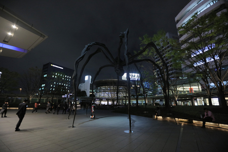 mori: A couple sit near the spider sculpture outside of Mori Tower Editorial