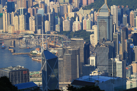overpopulated: Crowded Hong Kong skyline scene, green tropical mountain background