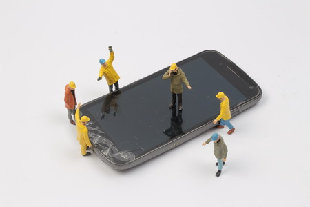 miniature worker on smart phone trying to service or working on cracked screen