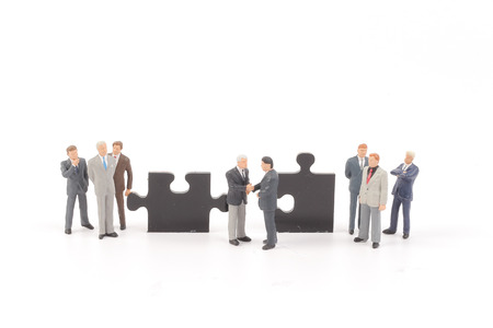 business puzzle: business people collaborate holding up jigsaw puzzle pieces