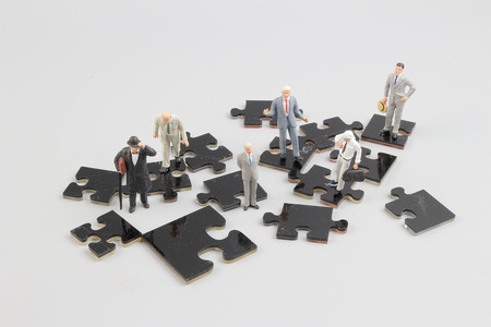 the business people collaborate holding up jigsaw puzzle pieces