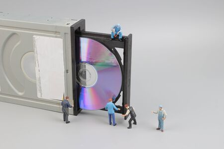 Selective focus of miniature engineer and worker fixed  CD rom