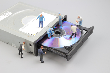 Selective focus of miniature engineer and worker fixed to clean CD rom