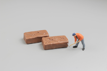 pices: the mini worker cut a pices of chocolate
