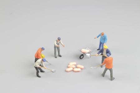 the worker figure in front of the pills 版權商用圖片