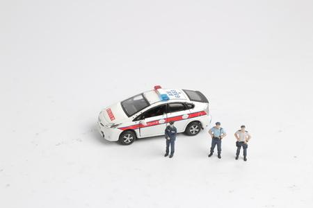 la figura de un policía y un coche de policía Foto de archivo