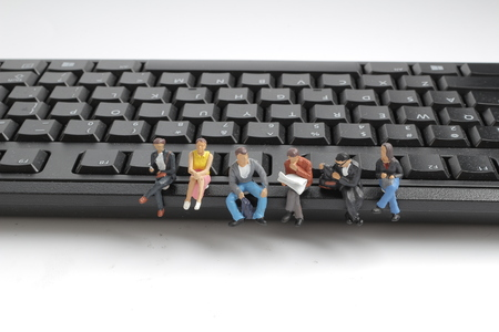 a mini workers sitting on top of keyboard. 版權商用圖片 - 90528338