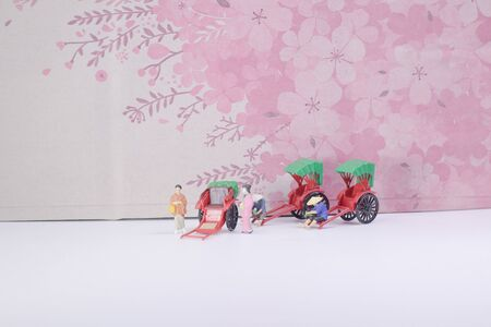 a Mini statue and red vintage oriental rickshaw cab