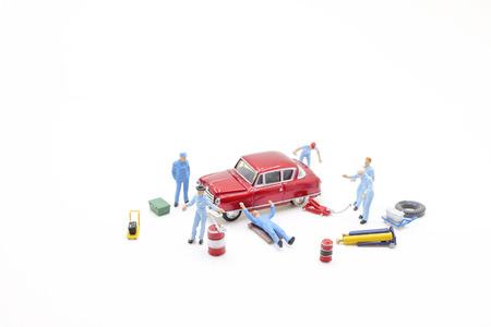 mini mechanics working on a car at the board
