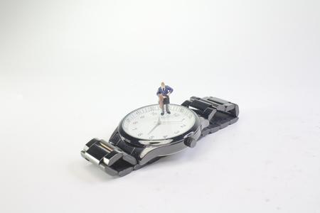 the mini business man figure standing on watch 版權商用圖片