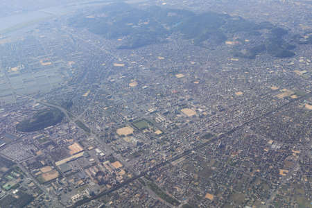 Aerial view of plane window looking down to land Stock Photo