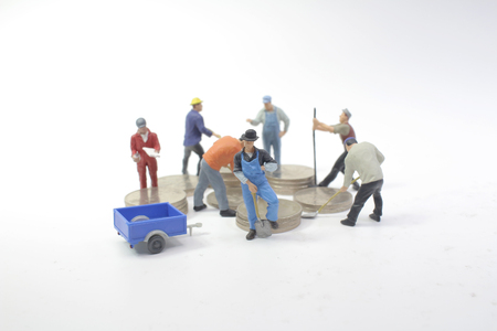 mini workers move coins. Growing a money 版權商用圖片