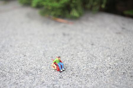the tiny of wheel chair figurine on stone surface Reklamní fotografie