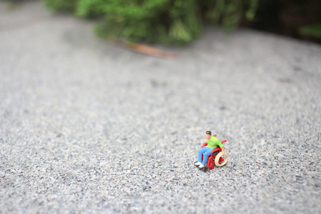 the tiny of wheel chair figurine  on stone surface