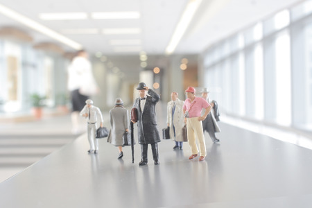 mini figures of people walking in the office corridor.