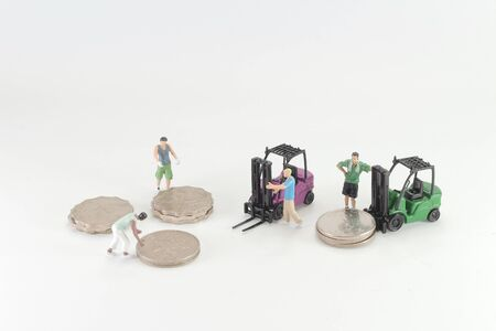 Mini figure of Men Moving A Stack Of Coins 写真素材