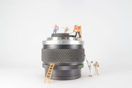 mini figure of workers clearing the mini lens.