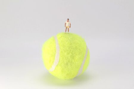 A Tiny toys play tennis on the big tennis Stock Photo