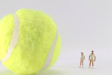A Tiny toys of tennis player and big tennis ball Stock Photo