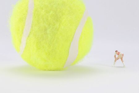 A Tiny toys of tennis player with big tennis ball Stock Photo