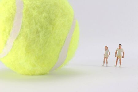 A Tiny toys of tennis player and  big tennis ball