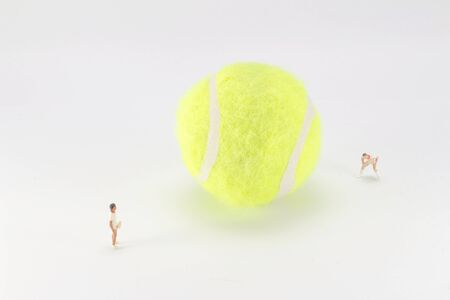 A Tiny toys play tennis and with the big tennis ball