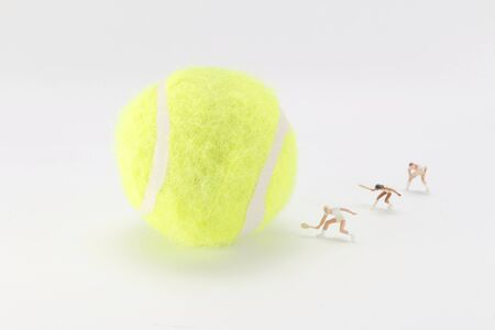 A Tiny toys playing tennis together and with the big tennis ball