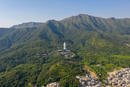 aerial view of Guanyin statue with mountain village in Hong Kong