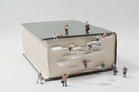 a miniature people mini figures with backpack walking and climbing on a mountain of textbooks