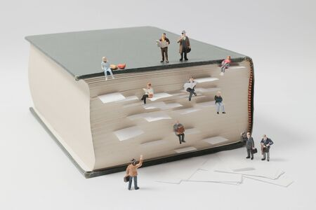 a miniature people mini figures with backpack walking and climbing on a mountain of textbooks Stock Photo